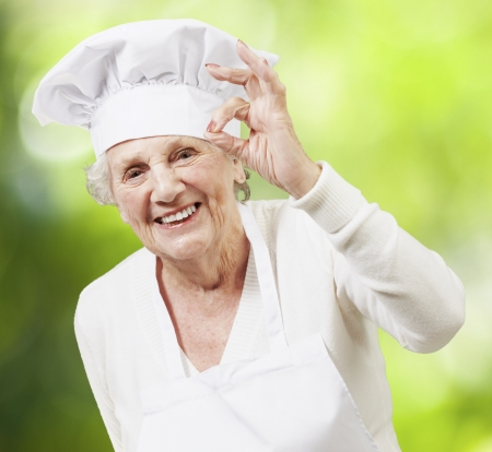 senior woman cook doing an excellent symbol against a nature background Stock fotó