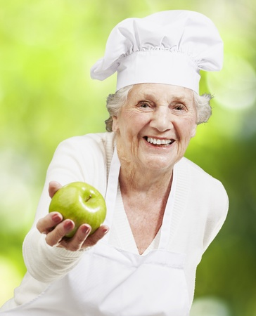 senior woman cook offering a green apple against a nature background photo