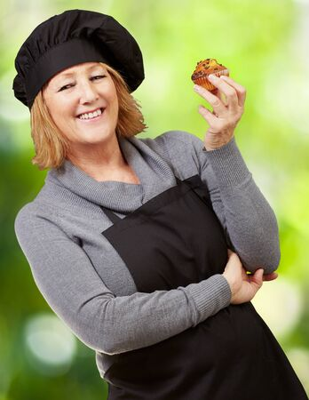 portrait of middle aged cook woman holding a homemade muffin against a nature background photo