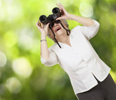 portrait of senior woman looking through a binoculars against a nature background photo