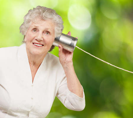 portrait of senior woman hearing with metal tin can against a nature background Stock Photo - 14438840