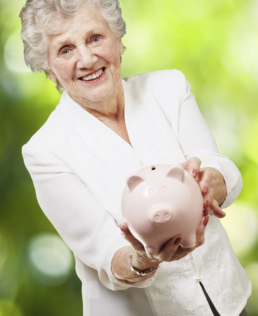 portrait of senior woman showing a piggy bank against a nature background photo