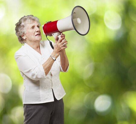 public service: portrait of senior woman holding megaphone over nature background Stock Photo