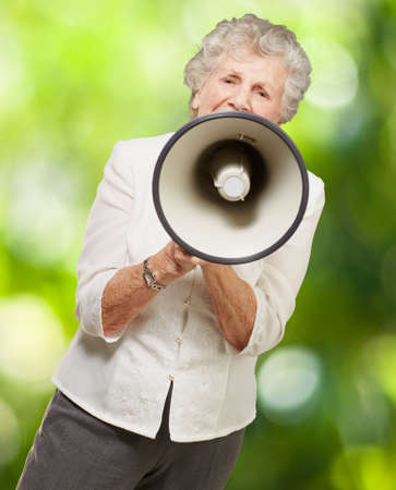 portrait of senior woman screaming with megaphone against a nature background photo