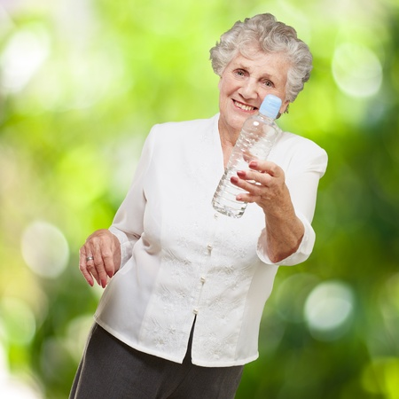 portrait of healthy senior woman holding a water bottle against a nature background photo