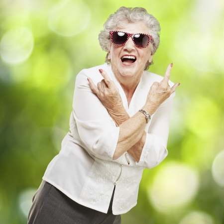 portrait of senior woman doing rock symbol against a nature background Stock Photo - 14438948