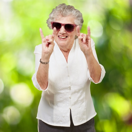 portrait of a happy senior woman doing rock symbol against a nature background Stock Photo - 14438909