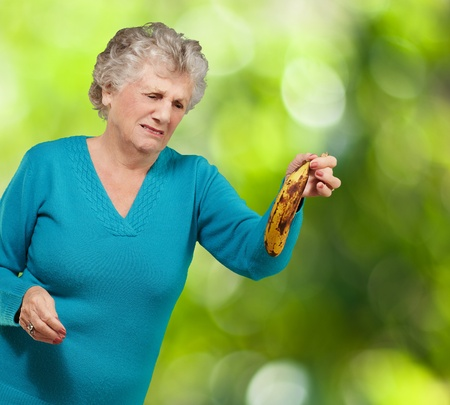 Senior woman holding a rotten banana against a nature background photo