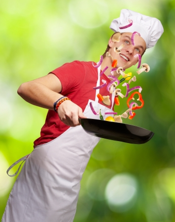 portrait of young cook man cooking vegetables against a nature background photo