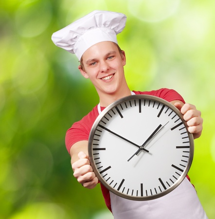portrait of young cook man holding clock against a nature background Stock Photo - 14438819