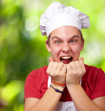 garden staff: portrait of young cook man screaming against a nature background