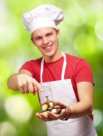 portrait of young cook man pressing a golden bell against a nature background photo