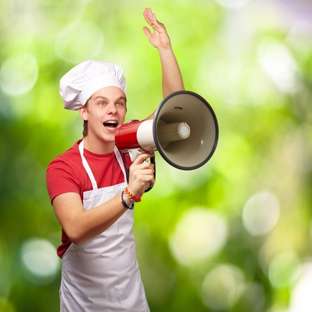 portrait of young cook man shouting with megaphone against a nature background photo