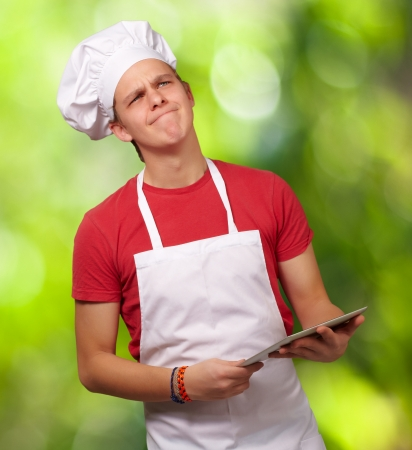 portrait of young cook man holding a digital tablet and thinking against a nature background photo