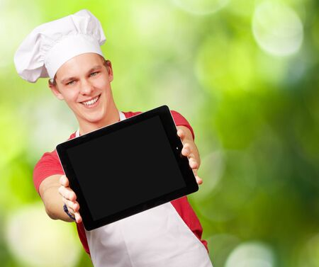 portrait of young cook man showing a digital tablet against a nature background photo