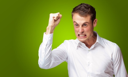 enrage: Portrait Of Angry Young Man Clenching His Fist Green Background