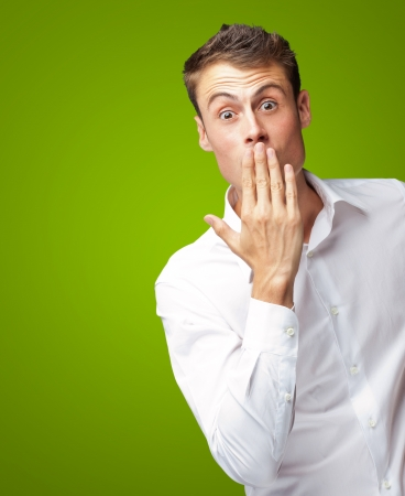 Portrait Of Young Man Covering His Mouth With Hand On Green Background photo