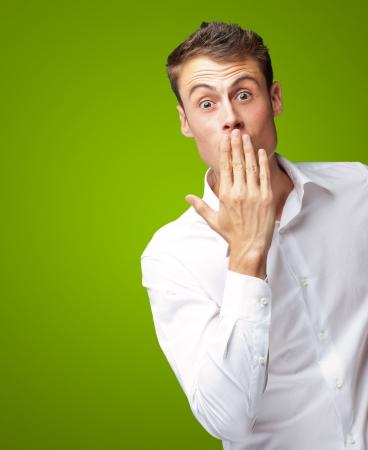 Portret Van Jonge Man die zijn mond met Hand Op Groene Achtergrond Stockfoto