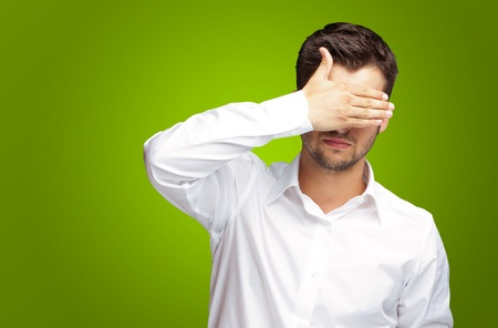 unsighted: Portrait Of An Businessman Covering Eyes Isolated On Green Background Stock Photo