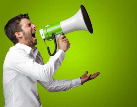 ruido: Retrato de un hombre gritando en un megáfono sobre fondo azul Foto de archivo
