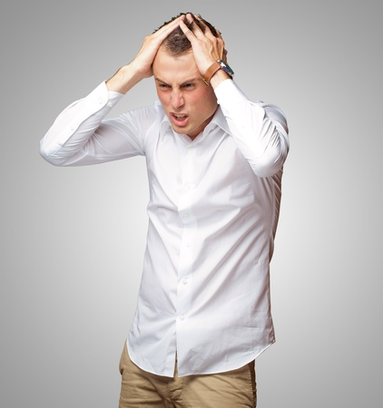 Portrait Of Stressed And Suffering Man On Gray Background photo
