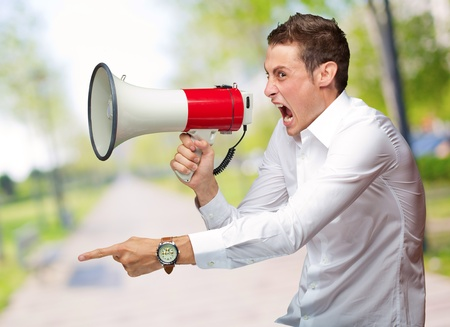 open shirt: Portrait Of Young Man Shouting On Megaphone, Outdoor Stock Photo