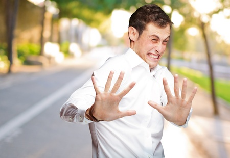 frightened: A Young Man Holding His Hands Out In Fear, Outdoor Stock Photo