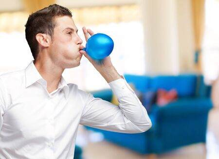Portrait Of Young Man Blowing Balloon, Indoor photo