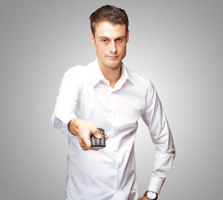 command button: Man Holding Remote In His Hand On Gray Background Stock Photo
