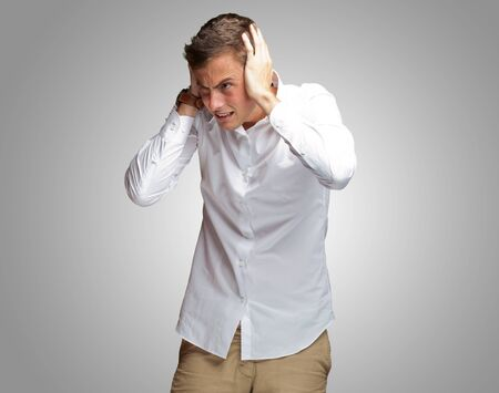 Portrait Of Young Man Covering His Ears With Hand On Gray Background Imagens