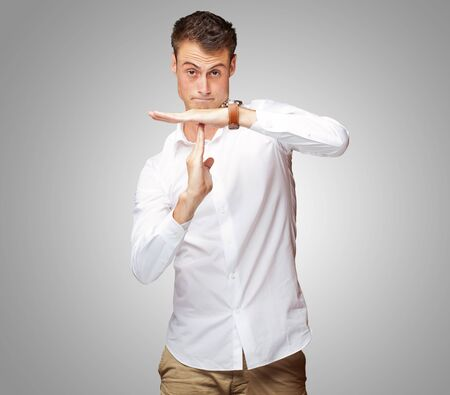 Portrait Of Young Man Gesturing Time Out Sign On Gray Background Stock Photo - 14706803
