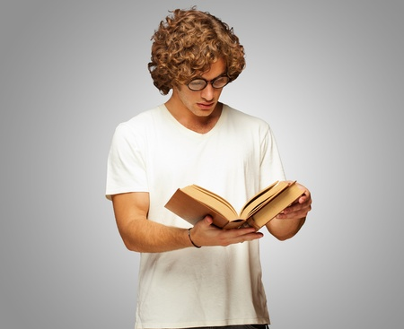 Portrait Of A Man Reading A Book Isolated On Grey Background photo