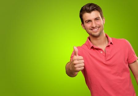 태도: 엄지 손가락으로 웃는 젊은 남자는 녹색 배경에 고립 스톡 사진