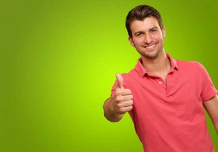 male's thumb: young man smiling with thumbs up isolated on green background
