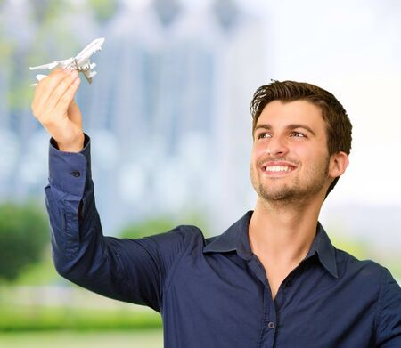 Man holding flag and miniature of airplane, outdoor photo
