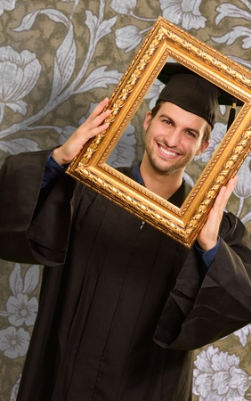 Graduate man looking through a frame, indoor Stock Photo - 14683277