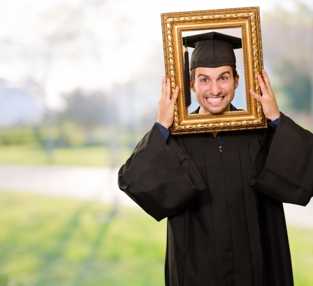 Graduate man looking through a frame, outdoor Stock Photo - 14683282