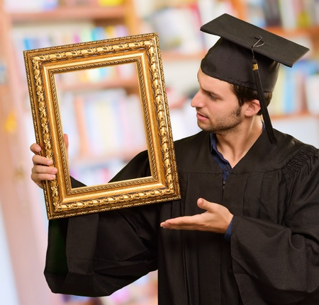 Graduate man showing a frame, indoor Stock Photo - 14683278