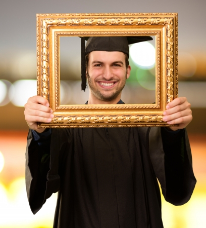 Graduate man looking through a frame, outdoor Stock Photo - 14706994