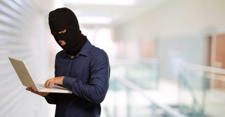 cyber crimes: young male thief holding laptop, indoor Stock Photo