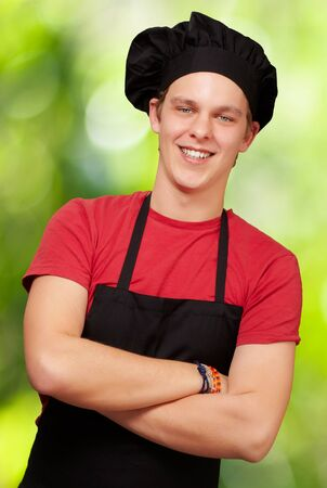 garden staff: portrait of young cook man wearing uniform and smiling against a nature background Stock Photo