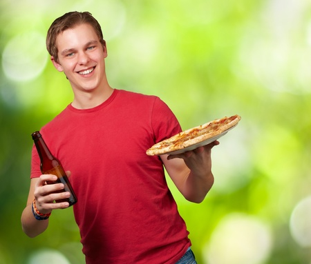 portrait of young man holding pizza and beer against a nature background photo