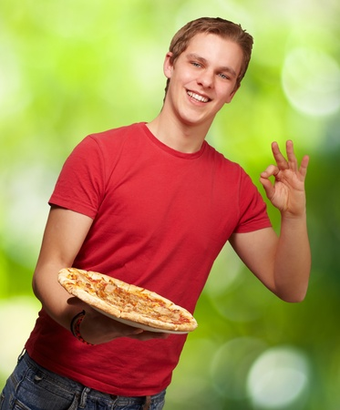 portrait of young man holding pizza and doing good gesture against a nature background photo