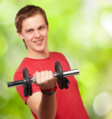 portrait of young man with weights against a nature background Stock Photo - 14703978