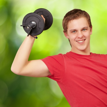 young man doing fitness with weights against a nature background Stock Photo - 14703935