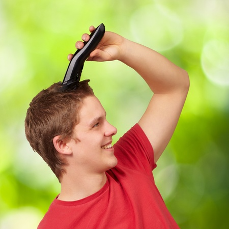 portrait of young man cutting his hair against a nature background Stock Photo - 14703980