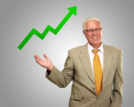 upward: Business Man Showing Graph Isolated On Gray Background Stock Photo