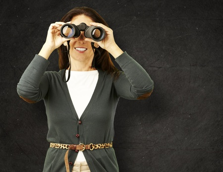 portrait of midlle aged woman looking with binoculars against a grunge wall Stock Photo - 14706924