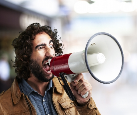 offer: portrait of young man shouting with megaphone at a crowded place
