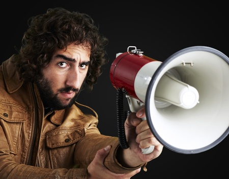 portrait of young man holding megaphone against a black background photo